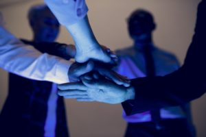 Hands join together in a group meeting